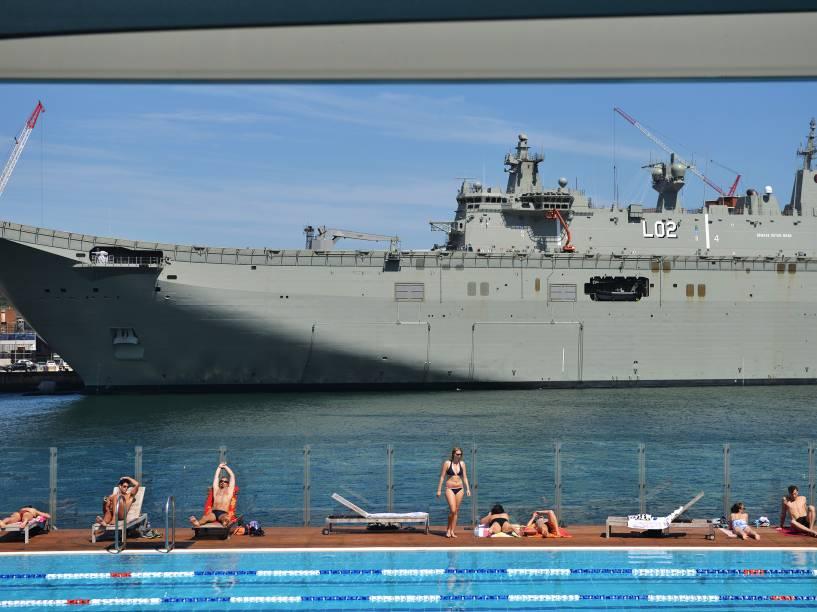 Pessoas tomaram banho de sol em uma piscina em frente ao HMAS Canberra, o mais recente navio de guerra da marinha de guerra australiana, atracado no Garden Island Naval em Sydney