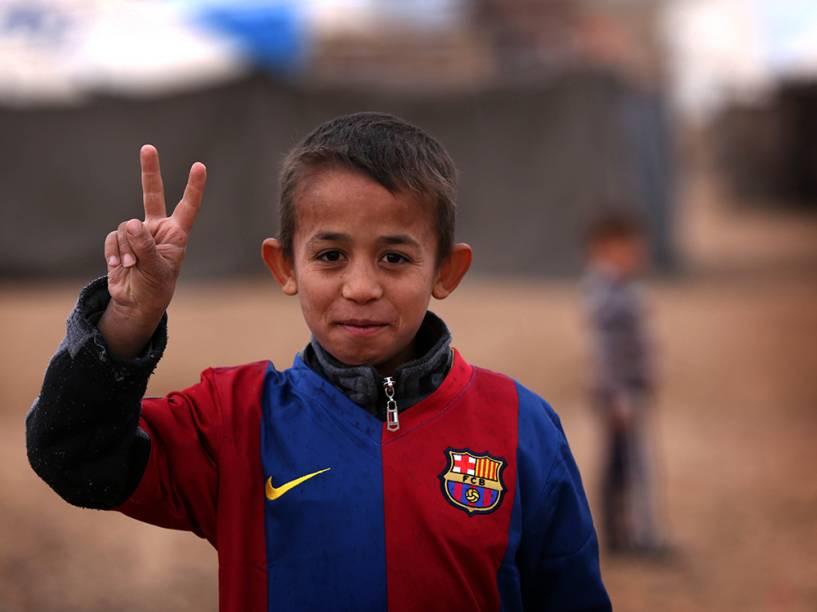 Criança iraquiana faz pose para foto com uma camisa do time espanhol Barcelona, no campo de refugiados de Harsham, região autónoma do Curdistão