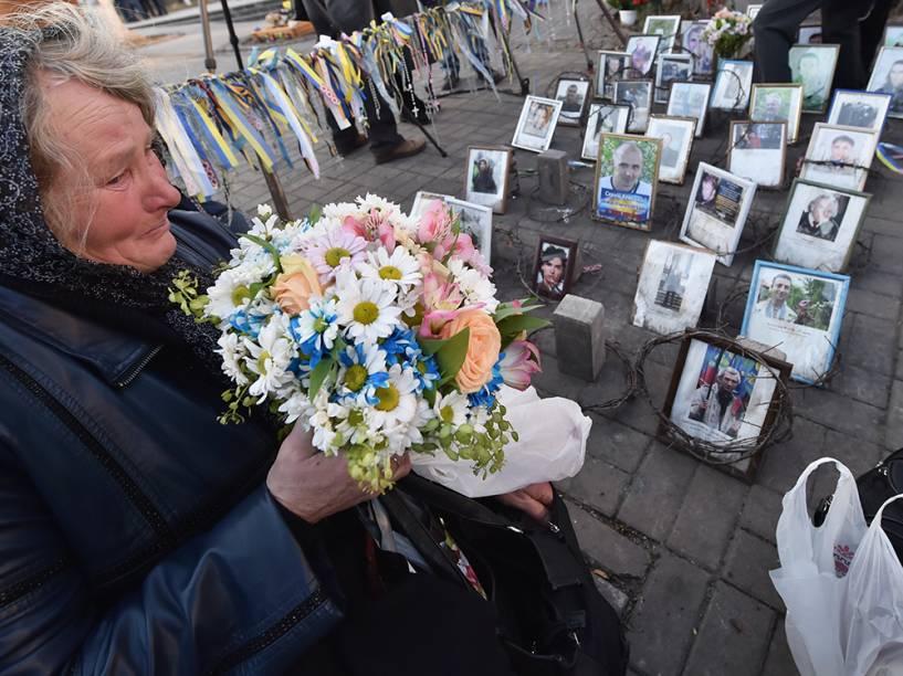 Mulher prende flores no Monumento de Heavenly Hundred, durante a cerimônia memorial em Kiev, na Ucrânia. Dezenas de pessoas se reuniram na Praça da Independência, deixando flores para as mais de 100 pessoas mortas nos confrontos separatistas desde o ano passado