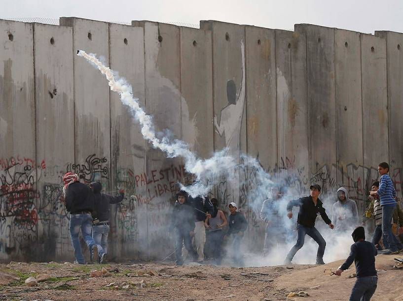 Manifestantes palestinos atiram bombas de gás em soldados israelenses durante confrontos anti-Israel, na Cisjordânia
