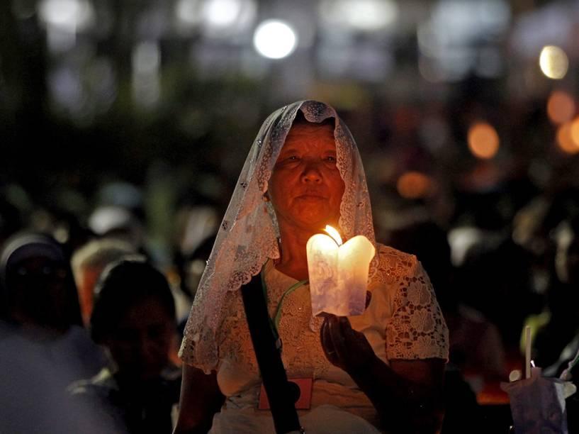 Devota cristã é fotografada segunda uma vela durante suas orações na igreja católica de St. Mary, em Rangum, na Birmânia
