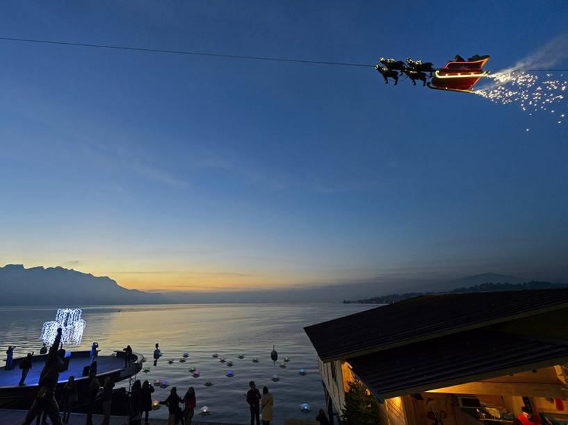 Um homem vestido de Papai Noel cumprimenta as pessoas de seu trenó conduzido por renas, no Lago de Genebra, durante o pôr-do-sol em Montreux, na Suíça