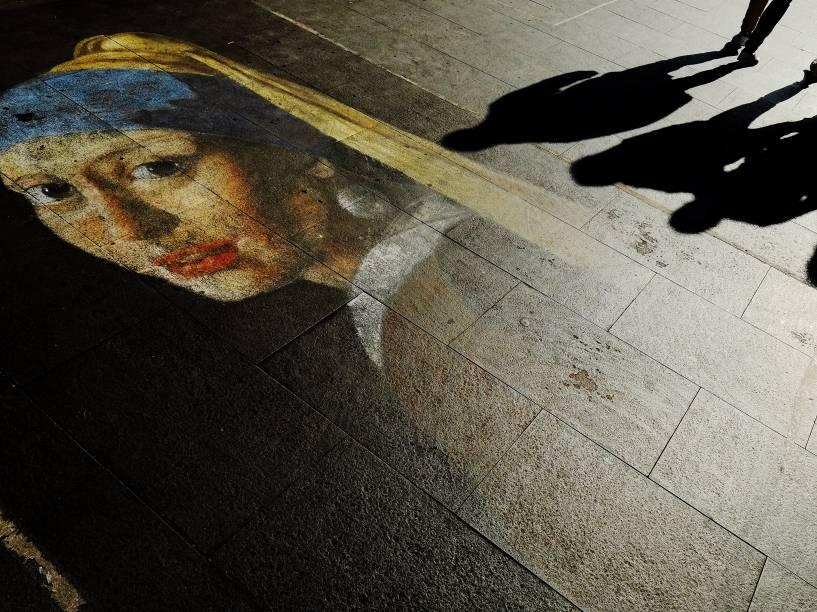 Pedestres caminham sobre um desenho que que reproduz a obra Moça com Brinco de Pérola, de Vermeer, no centro de Roma