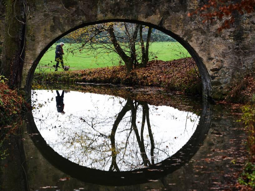 Mulher é refletida na água de um riacho  no parque estadual Hanau-Wilhelmsbad em Hanau, na Alemanha