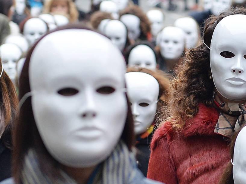 Grupo de mulheres com máscaras brancas no Dia Internacional para a Eliminação da Violência contra a Mulher, em Turim, na Itália