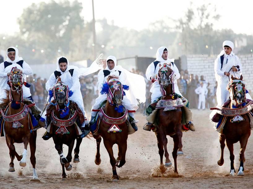 Homens vestindo roupas tradicionais andam a cavalo durante cerimônia de casamento, em Trípoli, na Turquia