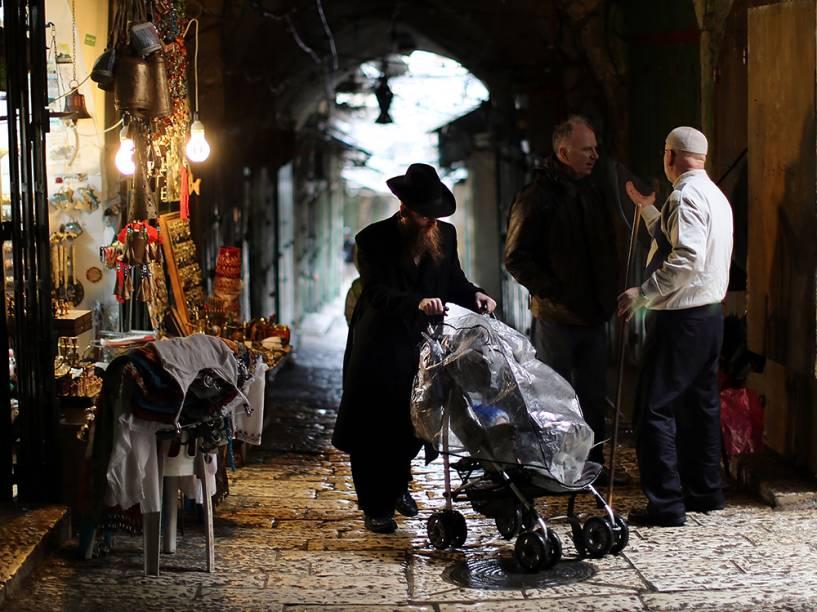 Um judeu caminha ao lado de comerciantes muçulmanos, na cidade velha de Jerusalém, em Israel