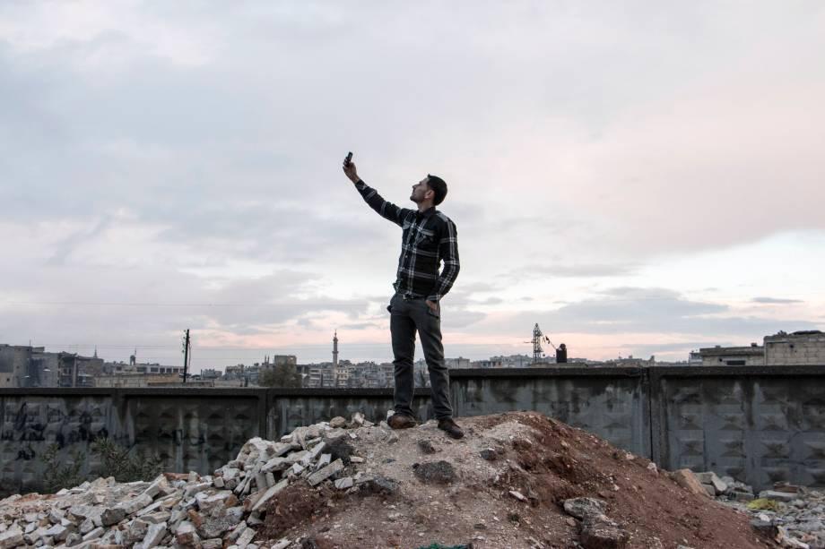 Um homem tentou obeter sinal de telefone subindo num morro em Aleppo. Mais de 200 mil pessoas morreram no território sírio desde o início do conflito em março de 2011, segundo a ONU