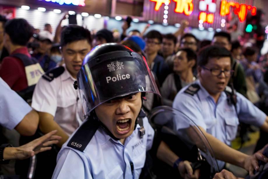 Policial chinês gritou na tentativa de conter manifestantes pró-democracia no distrito comercial de Mongkok, em Hong Kong, um dia após a polícia remover acampamentos de protesto no local
