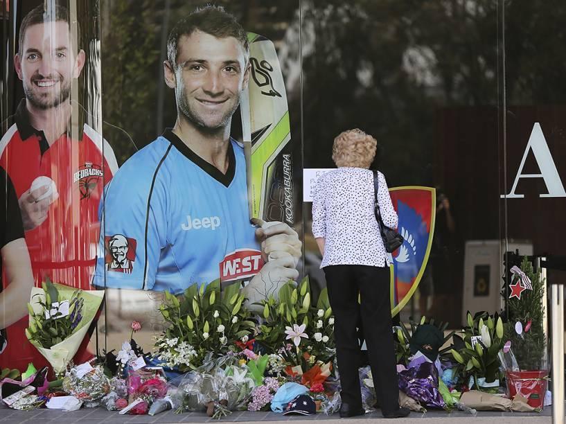 Mulher é vista deixando flores em homenagem ao atleta Phil Hughes, morto em um acidente durante uma partida de críquete, na cidade de Adelaide, na Austrália
