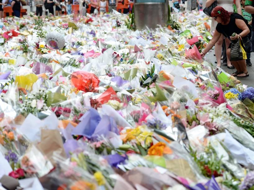 Australianos depositam flores em memorial improvisado em homenagem às vítimas do sequestro em cafeteria de Sydney nesta quinta-feira (18/12). Três pessoas foram mortas, incluindo o sequestrador