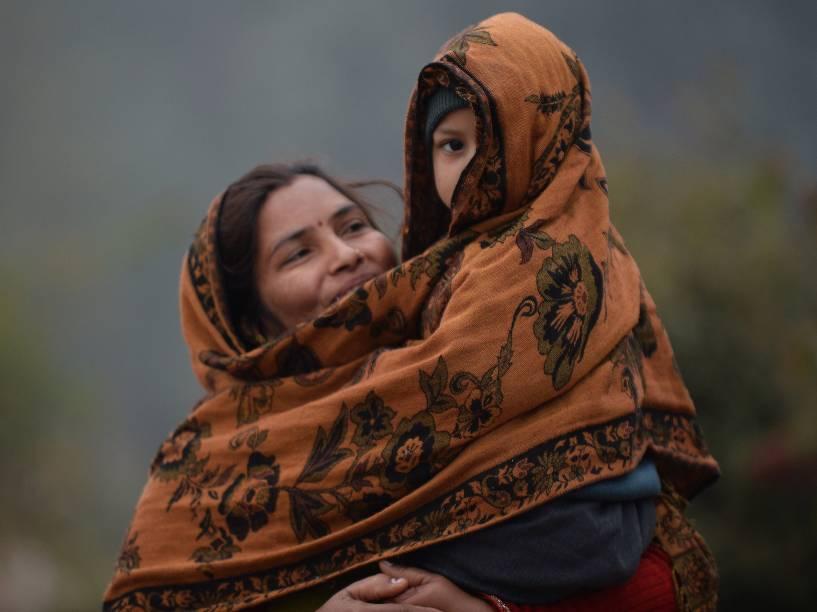 Mulher cobre o filho com um xale durante forte neblina que atingiu a cidade de Nova Délhi, pelo segundo dia consecutivo. O fenômeno reduziu a visibilidade para transportes na região, afetando rodovias, estradas de ferro e o tráfego aéreo na capital indiana