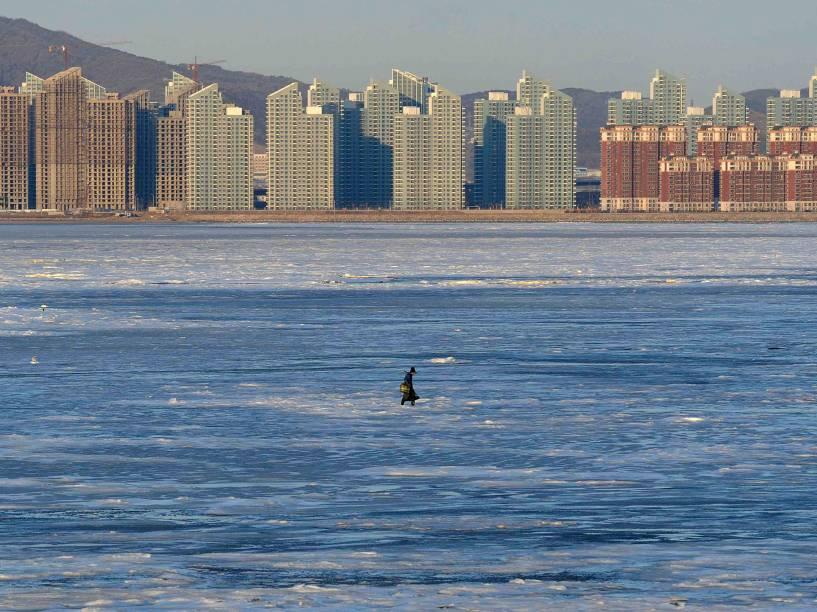 Um pescador caminha sobre a Baía de Jinzhou parcialmente congelada no Mar Bohai, em Dalian, na província de Liaoning, na China