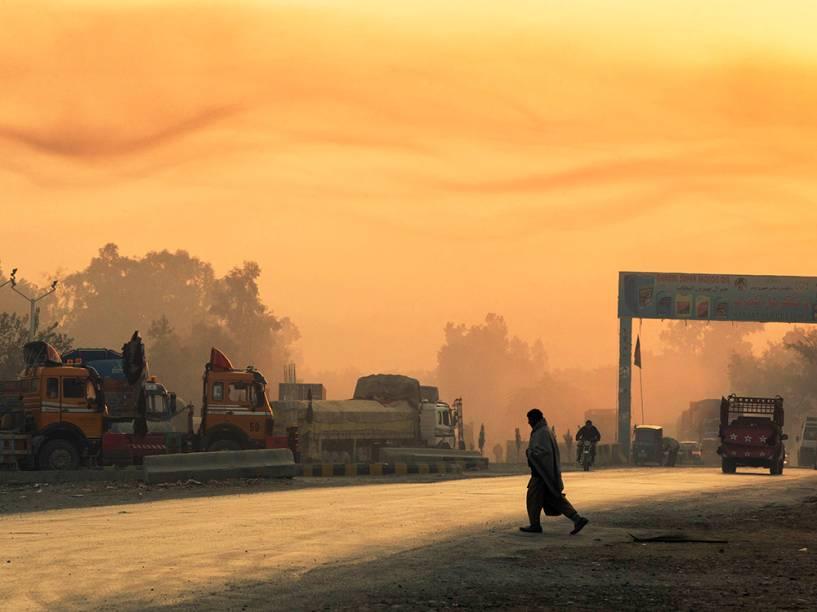 Homem atravessa a rua enquanto o dia amanhece nos arredores da Base Operacional de Fronte Fenty na província de Nangarhar, no Afeganistão 19/12/2014