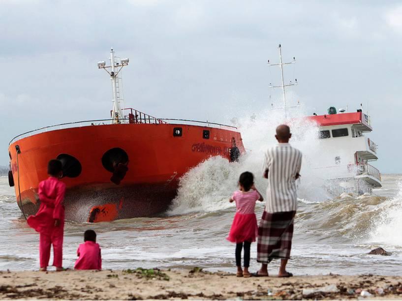 Pessoas assistem da praia as ondas atingem um navio indonésio que encalhou perto Narathiwat, no sul da Tailândia