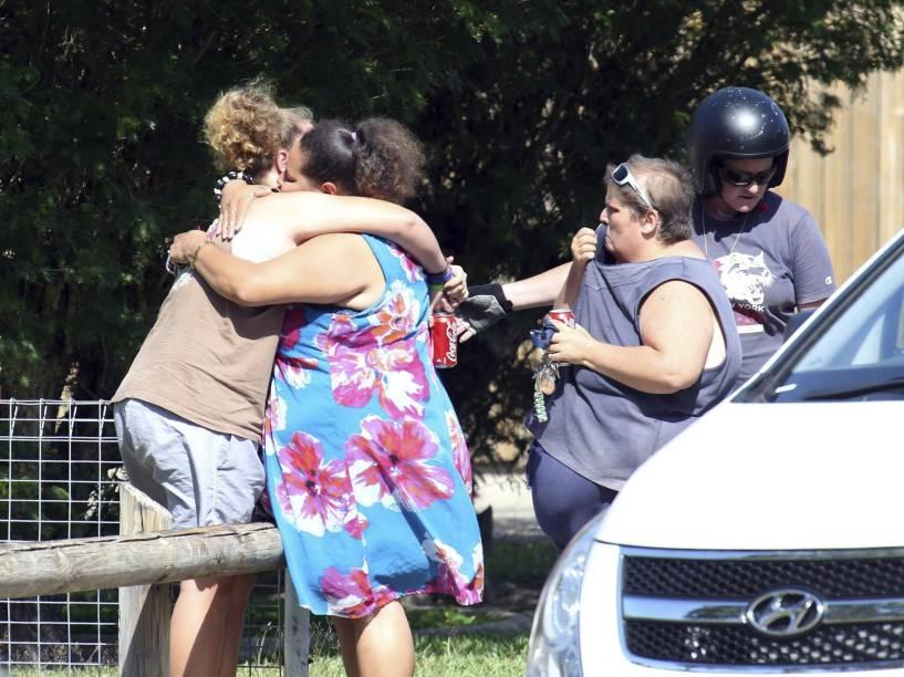 Mulheres choram em frente à casa onde foram encontradas oito crianças mortas a facadas na cidade de Cairns, no Estado de Queensland, na Austrália