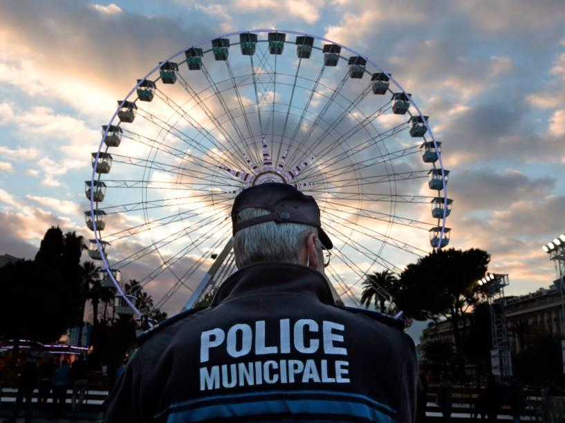 Um policial municipal fica de guarda nesta terça-feira (23/12) em uma roda-gigante enfeitada para celebrar o Natal em Nice, na França. As forças de segurança francesas intensificaram a proteção dos espaços públicos após três atos de violência em três dias, que deixaram cerca de 30 pessoas feridas e reacenderam os temores sobre a vulnerabilidade da França com ataques de radicais islâmicos