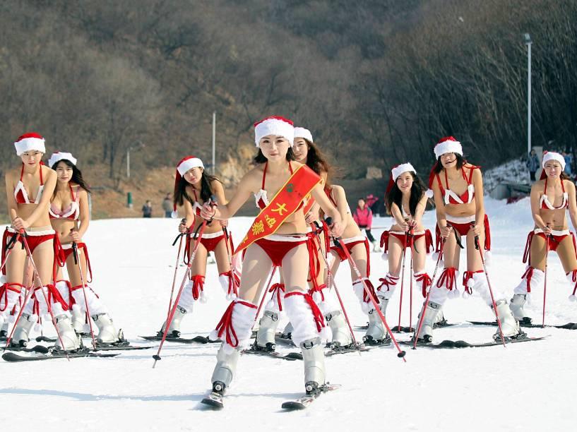 Mulheres de biquíni e gorro de Papai Noel participam de evento promocional de Natal em estação de ski em Xuchang, na China