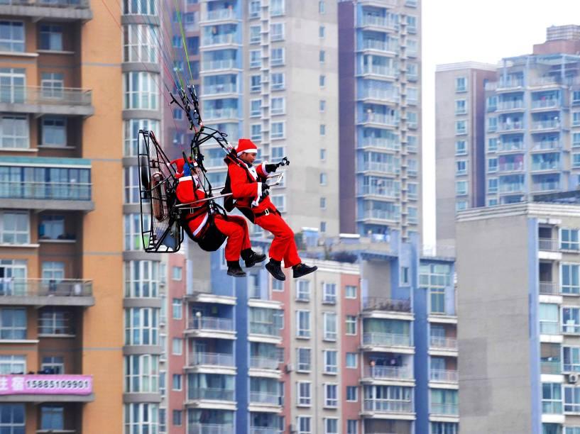 Homens fantasiados de Papai Noel voam com um paramotor voam próximos aos edifícios da cidade de Guiyang, na China, durante evento de comemoração do Natal