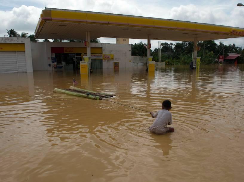Menino brinca próximo a um posto de gasolina coberto por água em Kota Bharu, na Malásia. O país enfrenta uma grave enchente que obrigou mais de 100 mil pessoas a deixarem suas casas