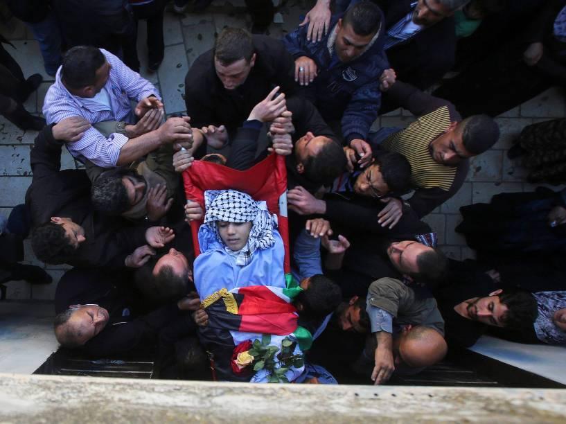 Homens carregam o corpo do palestino Imam Dwikat de 17 anos, morto a tiros por tropas israelenses, durante seu funeral na aldeia de Beita, na Cisjordânia. O jovem foi morto enquanto arremessava pedras em carros em uma rodovia ocupada na Cisjordânia - 30/12/2014