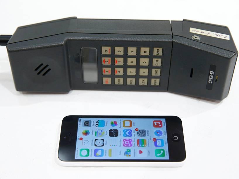 Uma foto-ilustração mostra um iPhone 5 ao lado de um telefone móvel na loja da Vodafone, em Oxford, durante um evento para marcar o 30º aniversário da primeira chamada de telefone móvel no Reino Unido