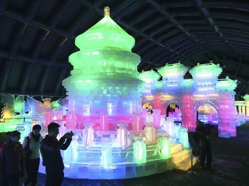 Algumas pessoas tiram fotografias de esculturas de gelo iluminadas com luzes coloridas durante um festival em Pequim, na China