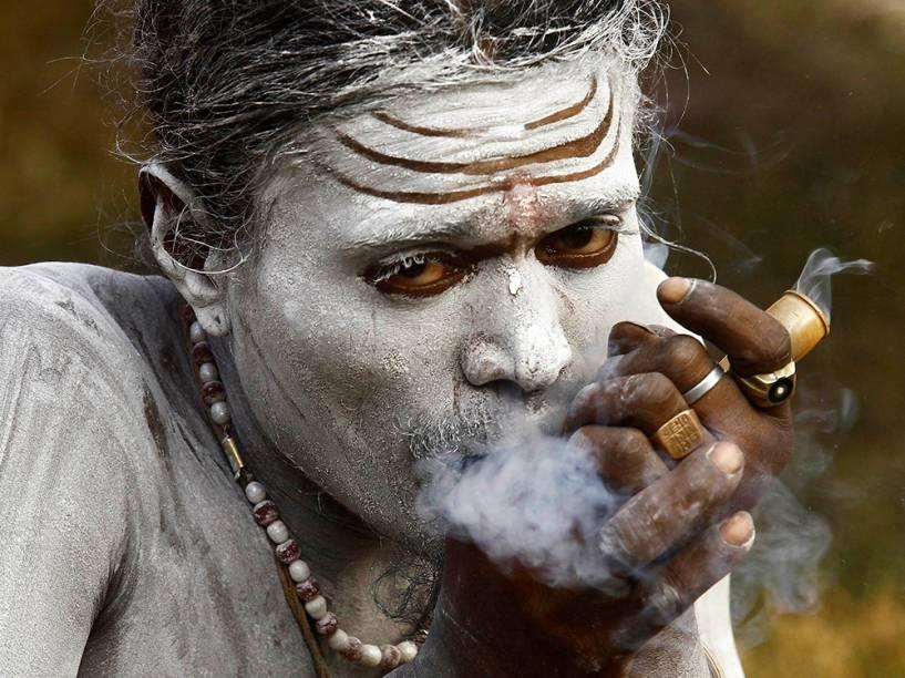 Hindu fuma ervas dentro de um abrigo improvisado nas margens do rio Ganges, durante a peregrinação anual para Sagar Island, na confluência do rio Ganges com a Baía de Bengala, na Índia