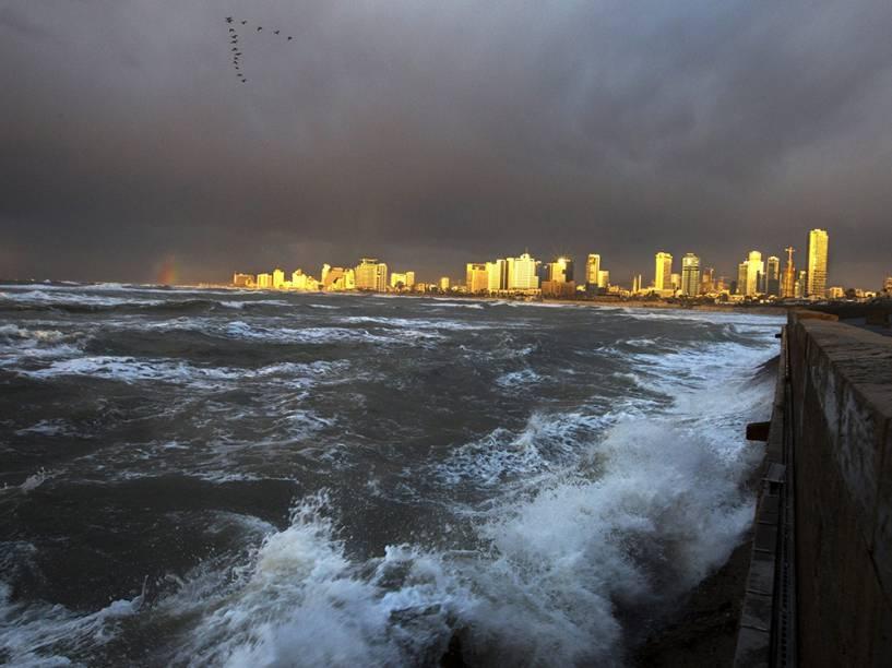 Sol ilumina os edifícios em Tel Aviv, capital de Israel, durante uma tempestade nesta quinta-feira (08)