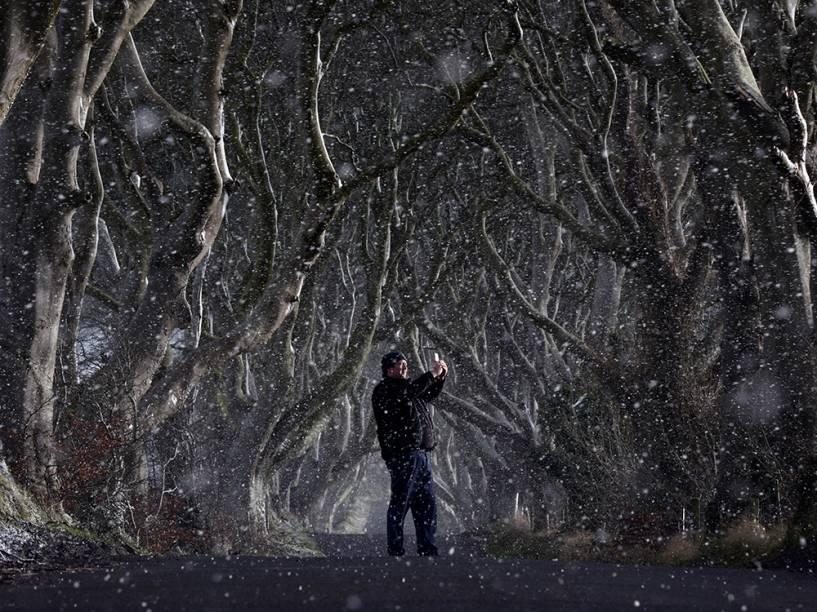 Na Irlanda do Norte, homem tira foto em meio a floresta enquanto neva na cidade de Antrim. O cenário ficou famoso após as gravações da série Guerra dos Tronos