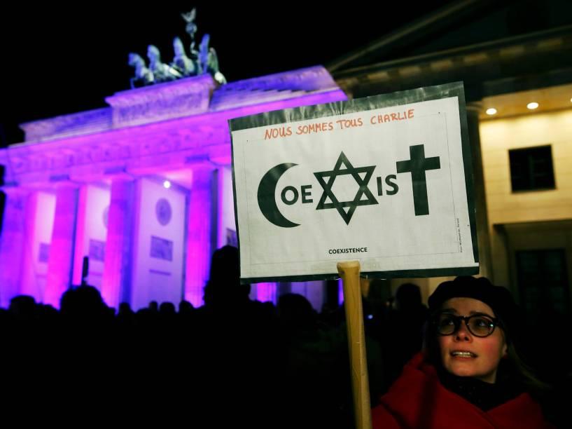 Mulher segura placa com os escritos Somos todos Charlie e a palavra coexistência, formada a partir de símbolos de diferentes religiões, em frente ao Portão de Brandemburgo, na Alemanha
