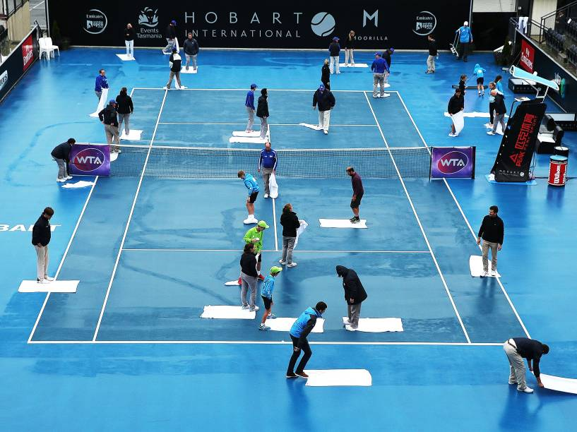 Diversos funcionários trabalham para secar a quadra antes de uma partida do torneio international de tênis, em Hobart, na Austrália - 14/01/2015