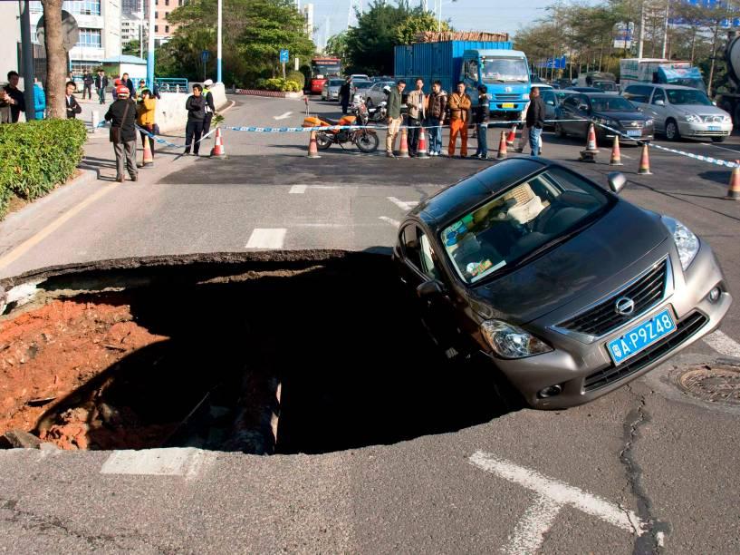 Um carro ficou pendurado à beira de uma cratera em Guangzhou, na China. Não foi esclarecido o que provocou a abertura do buraco, que tem mais de 5 metros de diâmetro. Ninguém ficou ferido