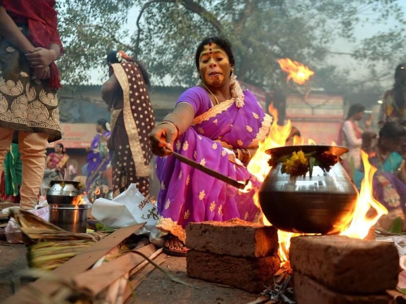 Devota hindu cozinha prato doce tradicional durante celebração do Pongal em Mumbai. O festival indiano em agradecimento pela colheita é celebrado no estado de Tamil Nadu