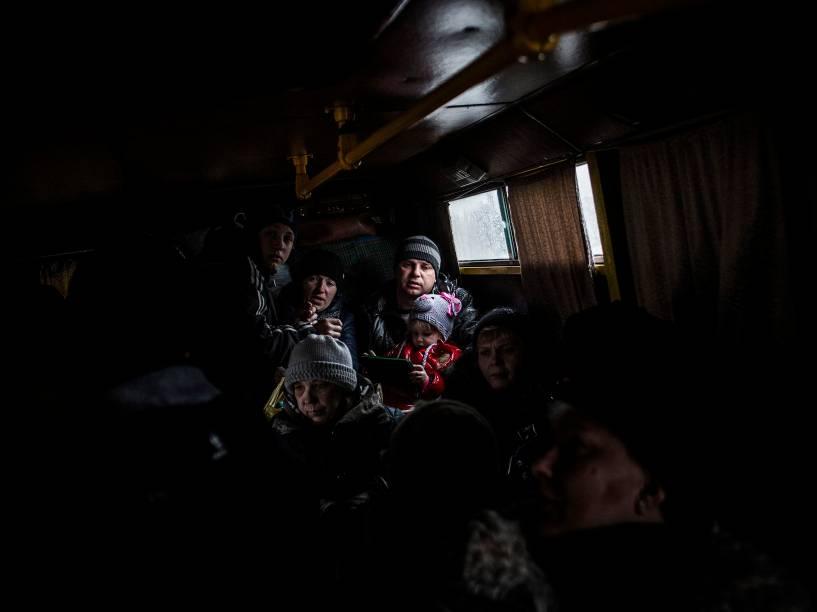Família tenta fugir em um ônibus da cidade ucraniana de Debaltseve, na região de Donetsk, disputada entre ucranianos e separatistas pró-Rússia