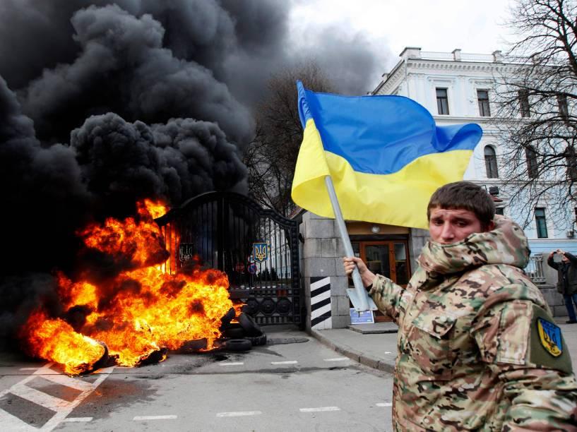 Combatente do batalhão Aydar balança bandeira ucraniana em frente ao Ministério de Defesa da Ucrânia, onde, momentos antes, foi ateado fogo, em Kiev