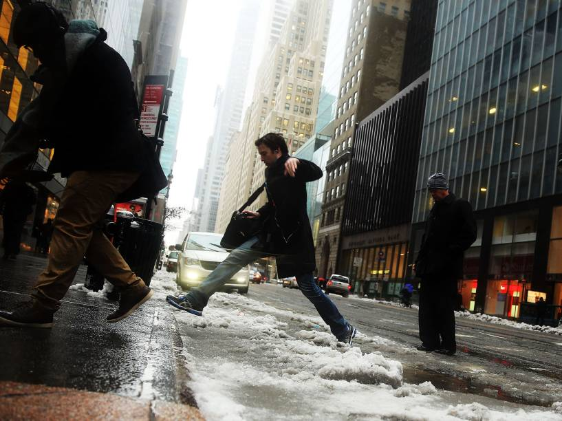 Homem pula possa de gelo para alcançar a calçada após tempestade de gelo que atingiu o bairro de Manhattan, em Nova York