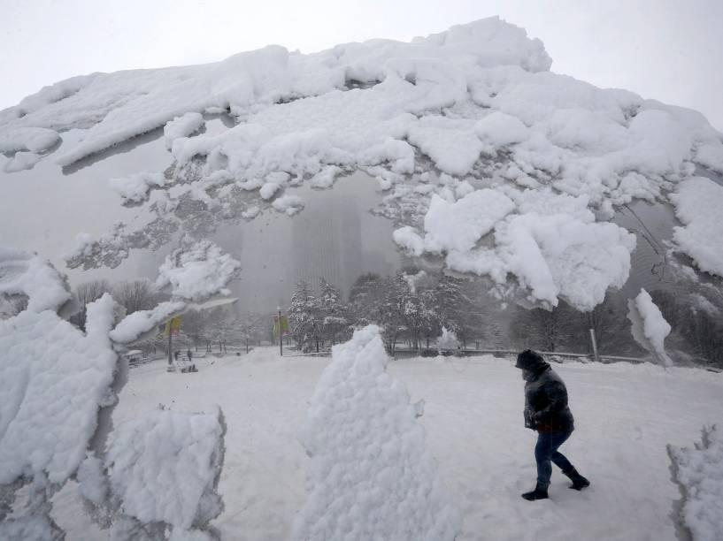 """Pedestre refletida na escultura """"Cloud Gate"""", que ficou coberta de neve após tempestade, no Millennium Park, em Chicago, nos Estados Unidos"""