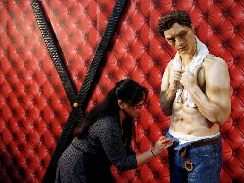 Confeiteira de bolos, Rosie Dummer, dá os toques finais ao bolo de tamanho real do personagem Christian Grey, do livro 50 Tons de Cinza, durante a abertura do show Cake International show em Manchester