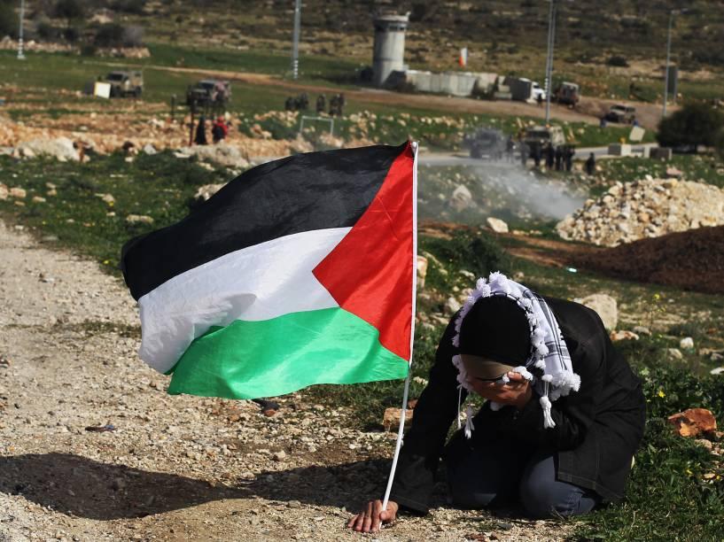 Mulher esconde seu rosto para se proteger de gás de pimenta, jogado por seguranças israelenses, enquanto segura sua bandeira palestina durante confronto após uma manifestação na Cisjordânia