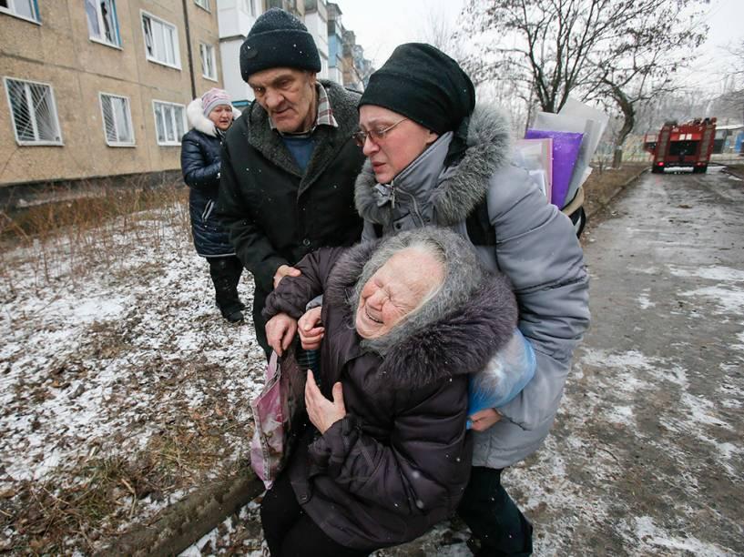 Idosa é acolhida após o prédio em que ela morava ser atingido por um bombardeio nos arredores de Donetsk, leste da Ucrânia