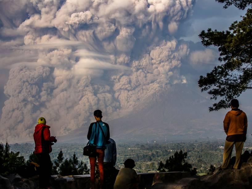 Moradores observam enorme nuvem de fumaça do vulcão Sinabung em Karo, na Indonésia