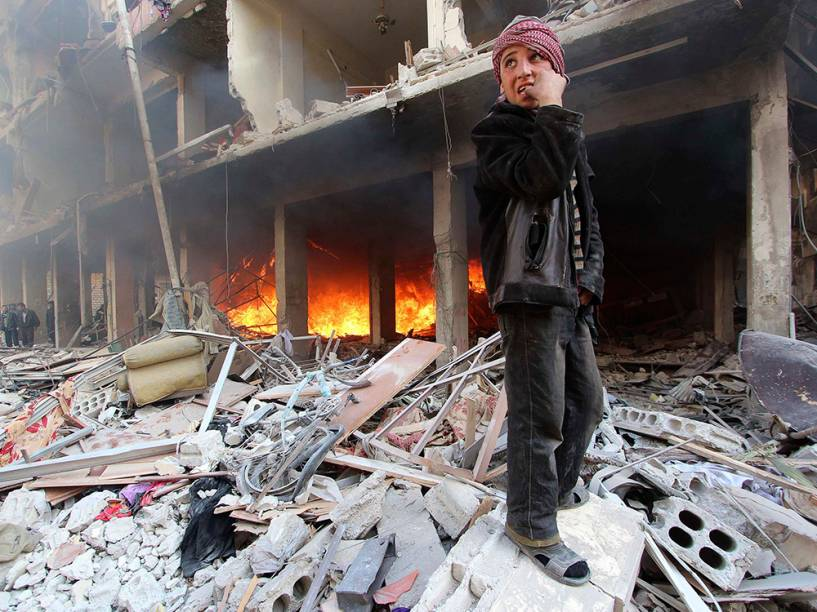 Menino anda por escombros em local atingido por um bombardeio das forças leais ao presidente da Síria, Bashar al-Assad no bairro de Douma, em Damasco