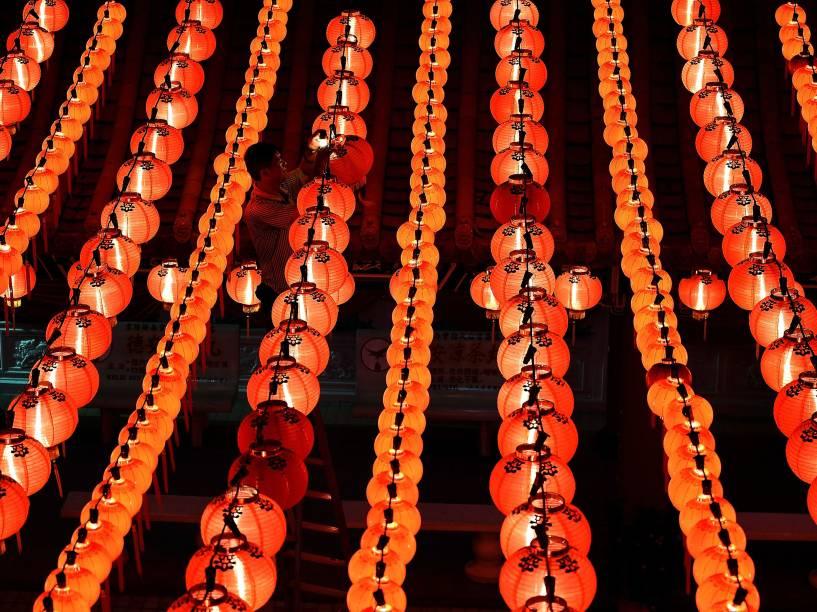 Homem conserta lanternas vermelhas antes da festa do Ano Novo Lunar chinês no Hou Temple Thean em Kuala Lumpur, na Malásia - 17/02/2015