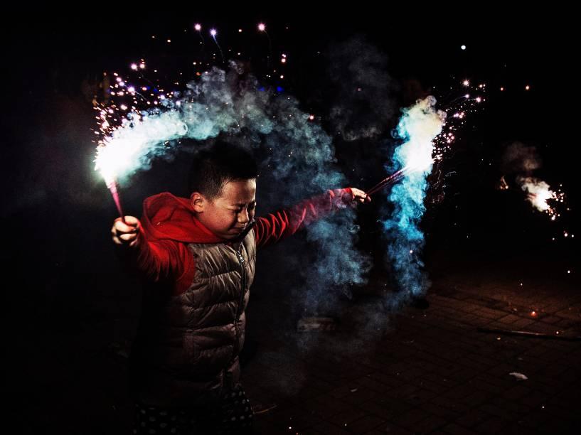 Menino chinês usa sinalizadores durante as comemorações do Ano Novo Lunar, em Pequim, China - 19/02/2015