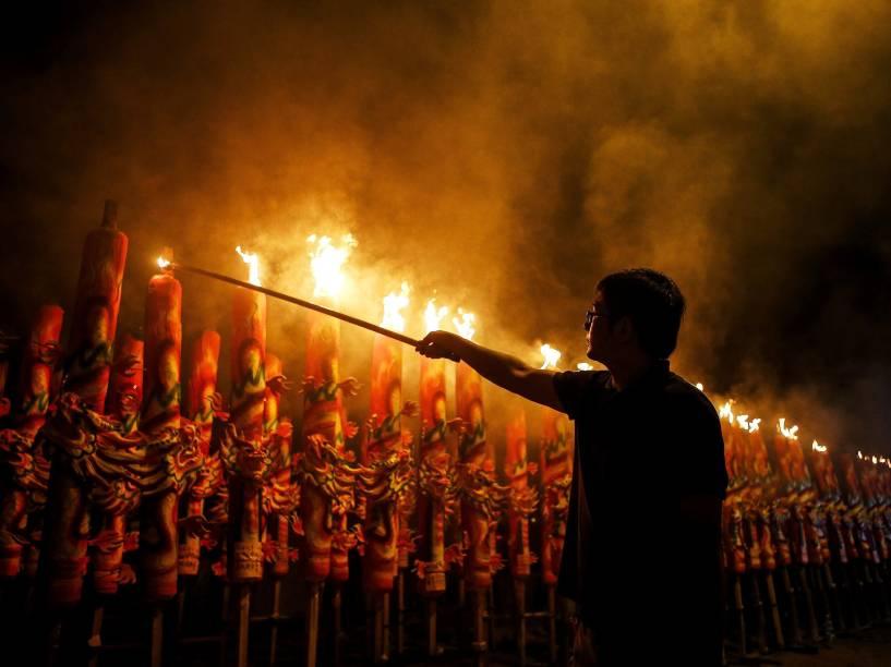 Homem acende pavis de incenso gigantes durante as celebrações do Ano Novo Chinês em Kajang, na Malásia