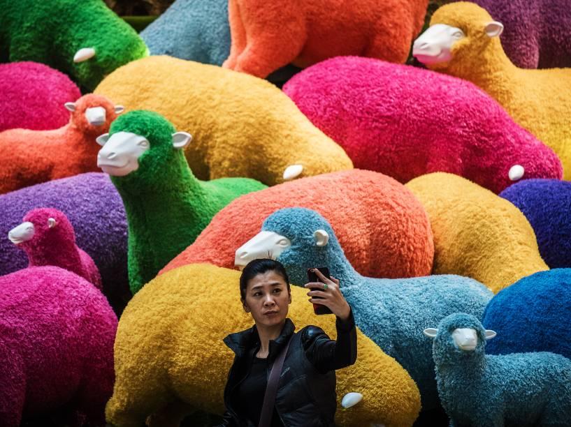 Mulher tira selfie em frente a ovelhas coloridas, postas a venda em shopping de Hong Kong para a celebração do Ano Novo Chinês