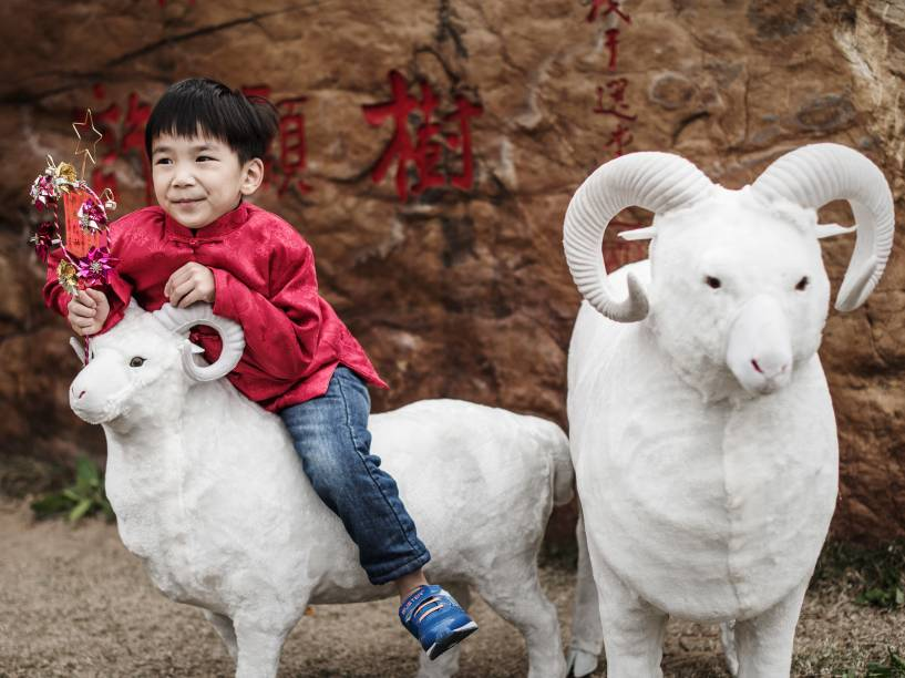 Durante as celebrações do primeiro dia do Ano Novo Lunar, menino monta em um modelo de carneiro, animal que representa 2015 para os Chineses