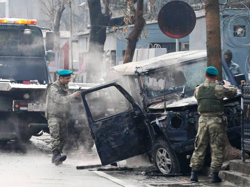 Soldados fotografam um veículo no local de um ataque suicida, em Cabul (Afeganistão). Um homem bateu seu veículo contra um carro carregado de explosivos da embaixada turca; uma pessoa morreu - 26/02/2015