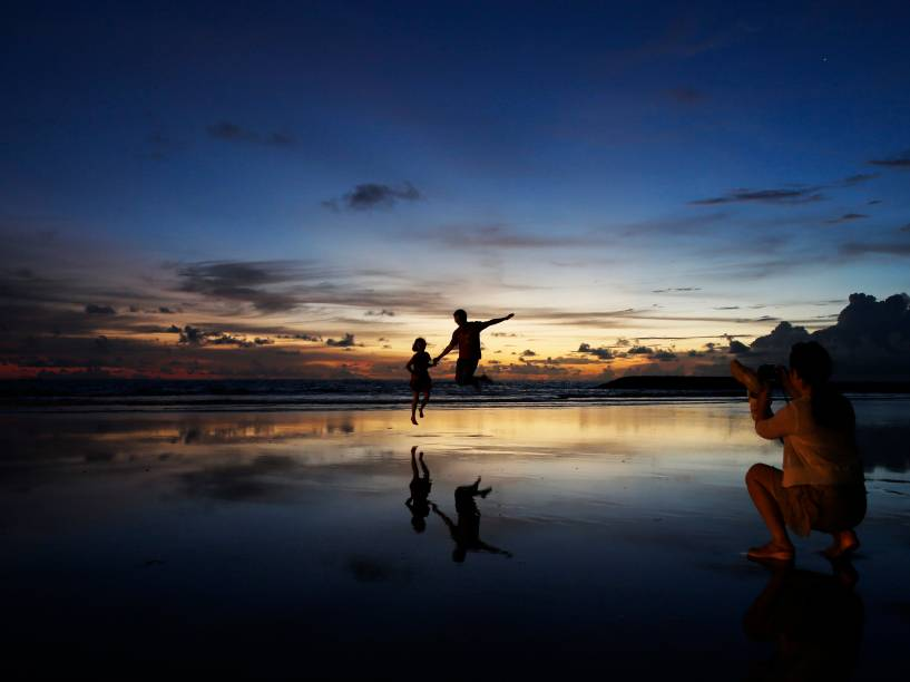 Mulher tira foto de seu marido e filho durante o pôr do sol na praia de Kuta, na Indonésia - 26/02/2015